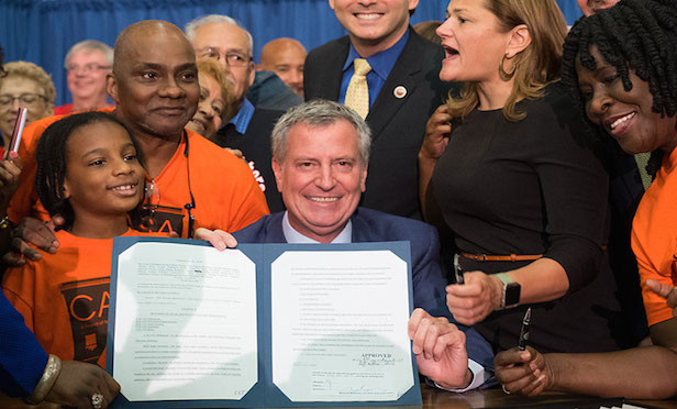 Mayor Bill de Blasio signed the tenant legal advocacy legislation on Friday.