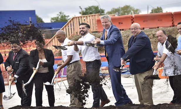 New York City Mayor Bill de Blasio and other city officials turned the first dirt at the new 1,000-seat school project in East New York.