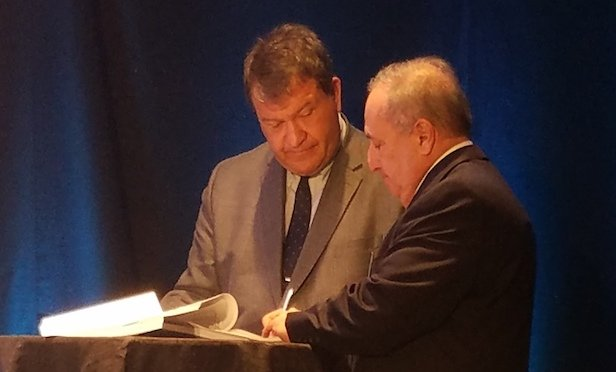 Westchester County Executive George Latimer (left) signs lease with Fareri Associates president John Fareri.