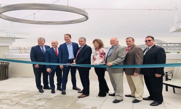 Bayonne officials joined Woodmont Properties executives at the ribbon cutting for Woodmont Bay Club.