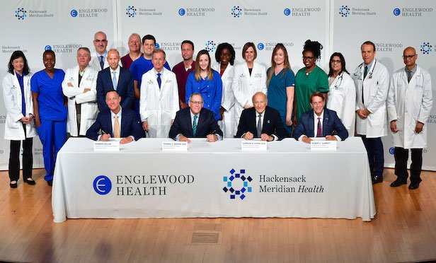 From left, (seated) Warren Geller, president and CEO, Englewood Health; Thomas C. Senter, Esq., chairman, Board of Trustees, Englewood Health; Gordon N. Litwin, Esq., chairman, Board of Trustees, Hackensack Meridian Health; and Robert C. Garrett, FACHE, CEO, Hackensack Meridian Health.