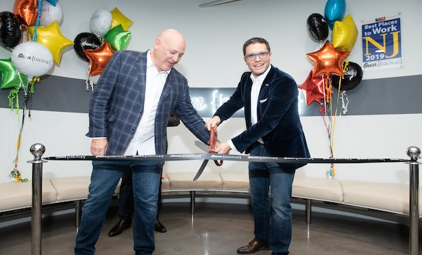 Charles Johnston, VP, sales, North America, at OwnBackup, and OwnBackup CEO Sam Gutmann cut the ribbon at the company's new Englewood Cliffs headquarters on Oct. 20.