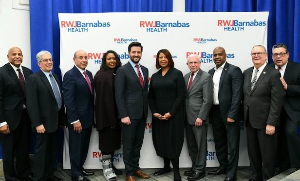 New Jersey Lt. Governor Sheila Oliver (center) joins other officials including NJHMFA Executive Director Charles Richman, Newark Mayor Ras J. Baraka, Barry H. Ostrowsky, president and CEO, RWJBarnabas Health, Jacob Fisher, regional VP, Pennrose, LLC, and other guests following the funding announcement.
